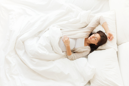 Photo pour pregnancy, rest, people and expectation concept - happy pregnant woman sleeping in bed at home - image libre de droit