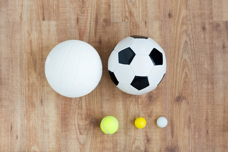 sport, fitness, game, sports equipment and objects concept - close up of different sports balls set on wooden floor from top