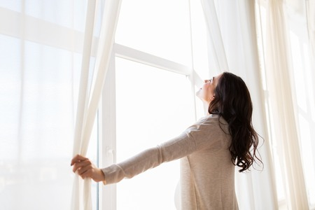 Photo for pregnancy, motherhood, people and expectation concept - close up of happy pregnant woman opening window curtains - Royalty Free Image