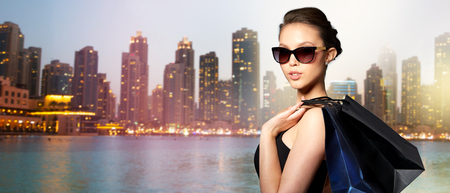 Photo for sale, tour, fashion, people and luxury concept - happy beautiful young woman in black sunglasses with shopping bags over dubai city night lights background - Royalty Free Image
