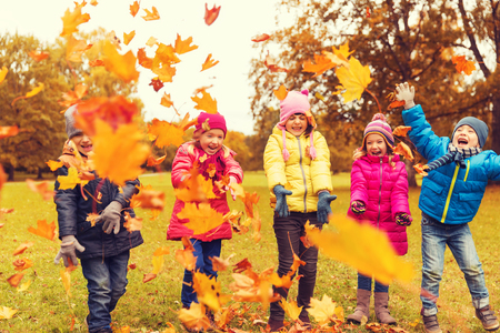 Foto de childhood, leisure, friendship and people concept - group of happy kids playing with autumn maple leaves and having fun in park - Imagen libre de derechos