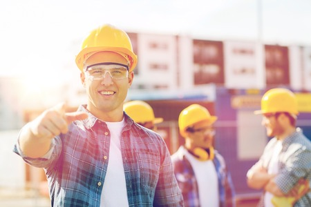 Photo for business, building, construction, gesture and people concept - group of smiling builders in hardhats pointing finger on you outdoors - Royalty Free Image