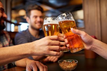 Foto de people, men, leisure, friendship and celebration concept - happy male friends drinking beer and clinking glasses at bar or pub - Imagen libre de derechos