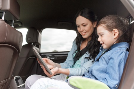 family, transport, road trip, travel and people concept - happy woman and little daughter with tablet pc computer driving in car