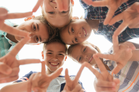 Photo for childhood, leisure, friendship and people concept - group of smiling happy children showing v sign in circle - Royalty Free Image