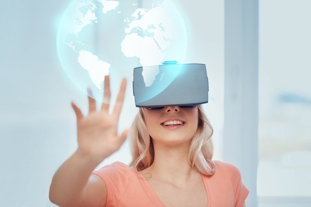 Photo pour technology, augmented reality, entertainment and people concept - happy young woman with virtual headset or 3d glasses playing game at home looking at projection of earth globe - image libre de droit