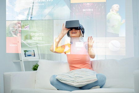 technology, augmented reality, media and people concept - happy young woman in virtual headset or 3d glasses and headphones looking at news projection at home