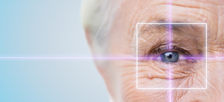 Foto de age, vision, surgery, eyesight and people concept - close up of senior woman face and eye with laser light - Imagen libre de derechos