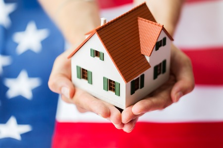 Photo pour citizenship, residence, property, real estate and people concept - close up of hands holding living house model over american flag - image libre de droit