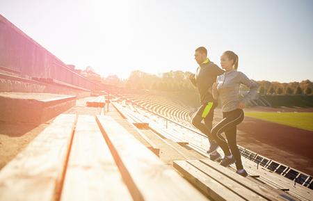 Foto de fitness, sport, exercising and lifestyle concept - happy couple running upstairs on stadium - Imagen libre de derechos