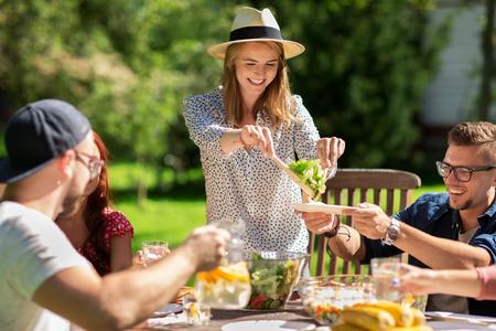 Foto de leisure, holidays, eating, people and food concept - happy friends having dinner and sharing salad at summer garden party - Imagen libre de derechos