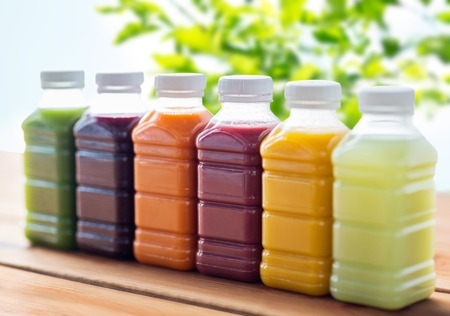 Photo pour healthy eating, drinks, dieting and packaging concept - plastic bottles with different fruit or vegetable juices on wooden table over green natural background - image libre de droit
