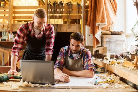Photo for profession, carpentry, woodwork and people concept - two carpenters with laptop computer and blueprint at workshop - Royalty Free Image