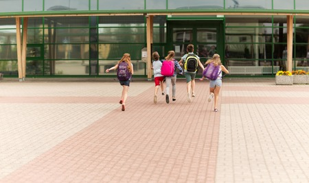 Photo pour primary education, friendship, childhood and people concept - group of happy elementary school students with backpacks running outdoors - image libre de droit
