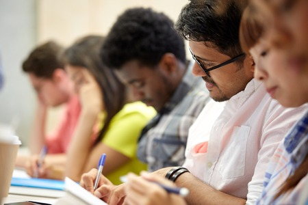 Photo pour education, high school, university, learning and people concept - group of international students writing at lecture - image libre de droit