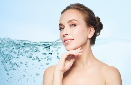 Photo for beauty, people and health concept - beautiful young woman touching her face over blue background with water splash - Royalty Free Image