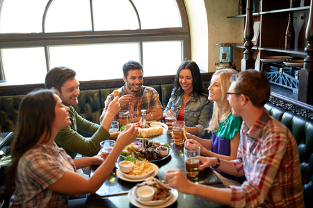 Photo for leisure, eating, food and drinks, people and holidays concept - smiling friends having dinner and drinking beer at restaurant or pub - Royalty Free Image
