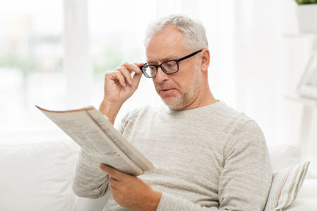 Photo pour leisure, information, people, vision and mass media concept - senior man in glasses reading newspaper at home - image libre de droit