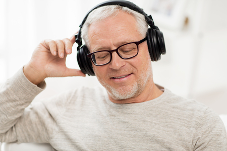 Photo for technology, people and lifestyle concept - close up of happy senior man in headphones listening to music at home - Royalty Free Image