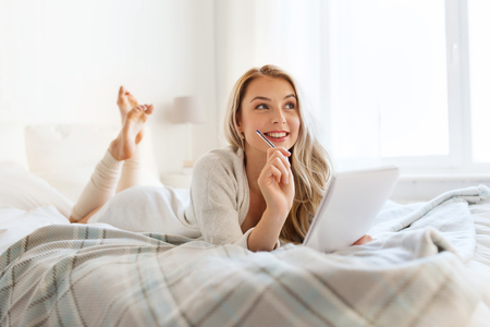 rest, inspiration, creativity, comfort and people concept - happy young woman with pen and notebook dreaming in bed at home bedroom