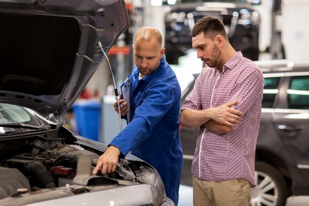 Photo pour auto service, repair, maintenance and people concept - mechanic with clipboard and man or owner looking at broken car engine at shop - image libre de droit