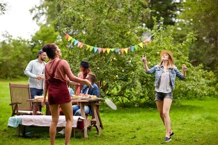 Foto de leisure, holidays, people and sport concept - happy friends playing badminton or shuttlecock at summer garden party - Imagen libre de derechos