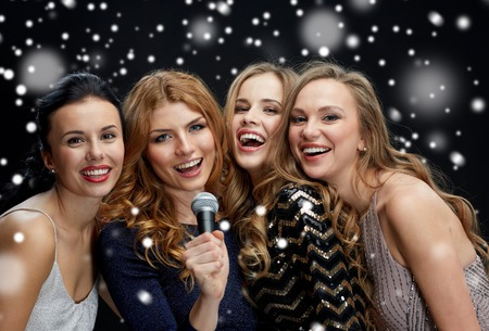 new year party, christmas, winter holidays and people concept - happy women with microphone singing karaoke over black background with snowの写真素材