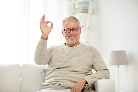 old age, gesture, comfort and people concept - smiling senior man in glasses sitting on sofa and showing ok hand sign at home