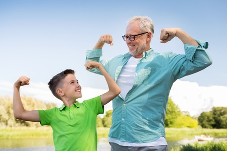 Photo pour family, generation, power and people concept - happy grandfather and grandson showing muscles - image libre de droit