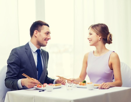 Photo for restaurant, couple and holiday concept - smiling couple eating sushi at restaurant - Royalty Free Image