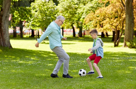 Photo pour family, generation, game, sport and people concept - happy grandfather and grandson playing football at summer park - image libre de droit
