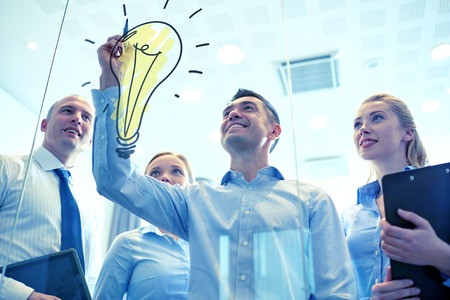 Foto de business, people, teamwork and planning concept - smiling business team with marker and light bulb doodle working in office - Imagen libre de derechos