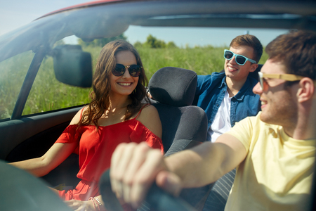 Photo pour leisure, road trip, travel and people concept - happy friends driving in cabriolet car along country road - image libre de droit