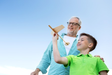 family, generation, future, dream and people concept - happy grandfather and grandson with toy airplane over blue sky