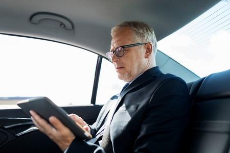 Photo pour transport, business trip, technology and people concept - senior businessman with tablet pc computer driving on car back seat - image libre de droit