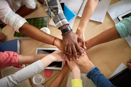 Photo pour education, school, teamwork and people concept - close up of international students with hands on top of each other sitting at table - image libre de droit