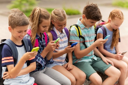 Foto de primary education, friendship, childhood, technology and people concept - group of happy elementary school students with smartphones and backpacks sitting on bench outdoors - Imagen libre de derechos