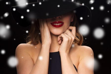 Foto de people, christmas, holidays, luxury and fashion concept - beautiful woman in hat over black background and snow - Imagen libre de derechos