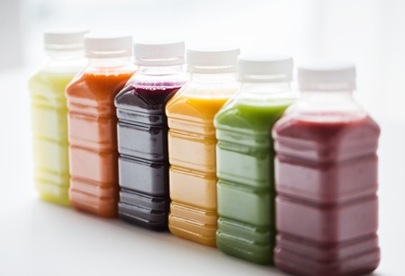 Foto de healthy eating, drinks, diet and detox concept - close up of plastic bottles with different fruit or vegetable juices on white - Imagen libre de derechos
