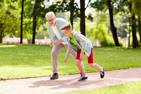 Photo pour family, generation and people concept - happy grandfather and grandson racing at summer park - image libre de droit