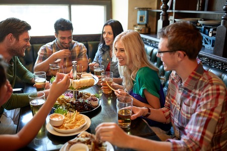 Foto de leisure, eating, food and drinks, people and holidays concept - smiling friends having dinner and drinking beer at restaurant or pub - Imagen libre de derechos