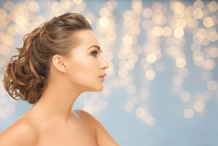 Photo for health, people, plastic surgery, holidays and beauty concept - beautiful young woman face over lights background - Royalty Free Image