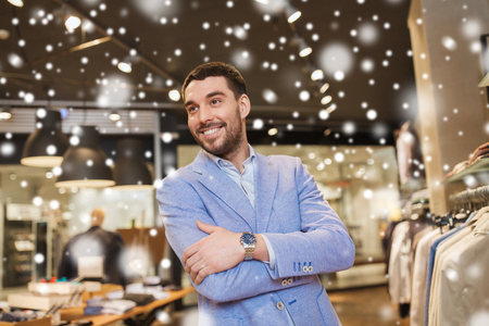 sale, shopping, fashion, style and people concept - happy young man in jacket at clothing store over snow