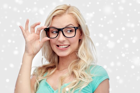 Photo pour vision, education and people concept - happy smiling young woman or teenage girl glasses over snow - image libre de droit