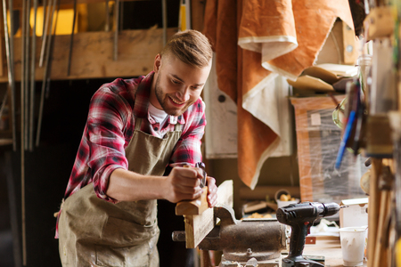 Photo pour profession, people, carpentry, woodwork and people concept - happy carpenter with jointer planing wood plank at workshop - image libre de droit