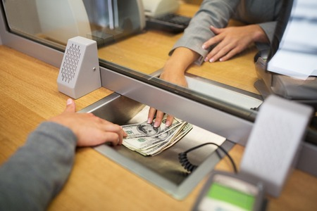 Photo pour people, withdrawal, saving and finance concept - clerk giving cash money to customer at bank office or currency exchanger - image libre de droit