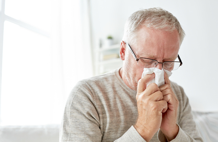 sick senior man with paper wipe blowing his nose