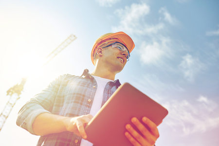 Photo for builder in hardhat with tablet pc at construction - Royalty Free Image