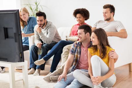 Photo pour happy friends with popcorn watching tv at home - image libre de droit