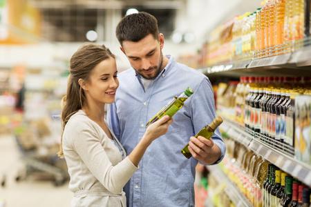 Photo pour happy couple buying olive oil at grocery store - image libre de droit